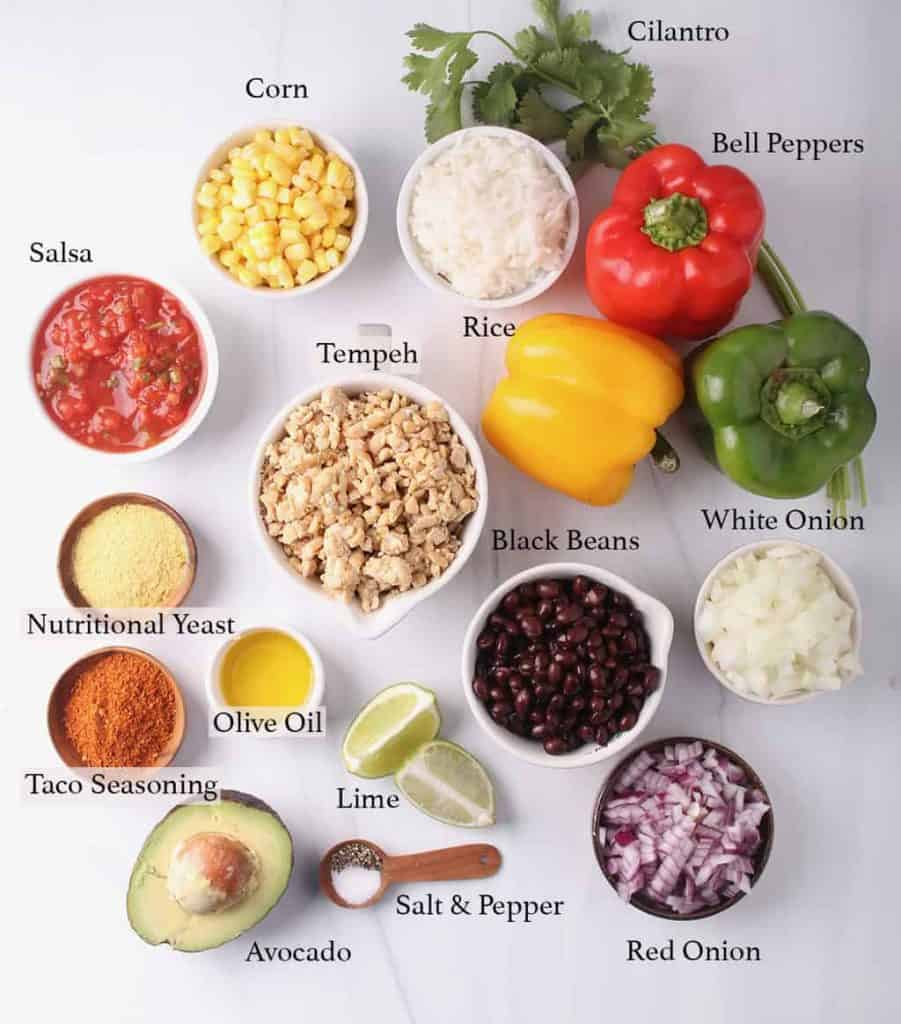 Ingredients for stuffed bell peppers, measured out in small white bowls.