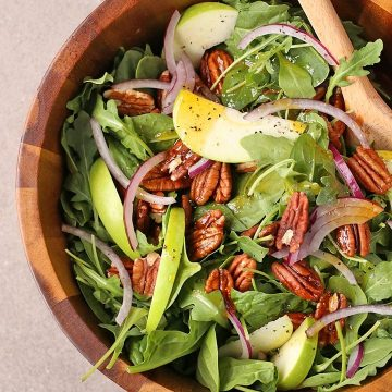 Curry Apple Salad in a salad bowl with wooden spoons
