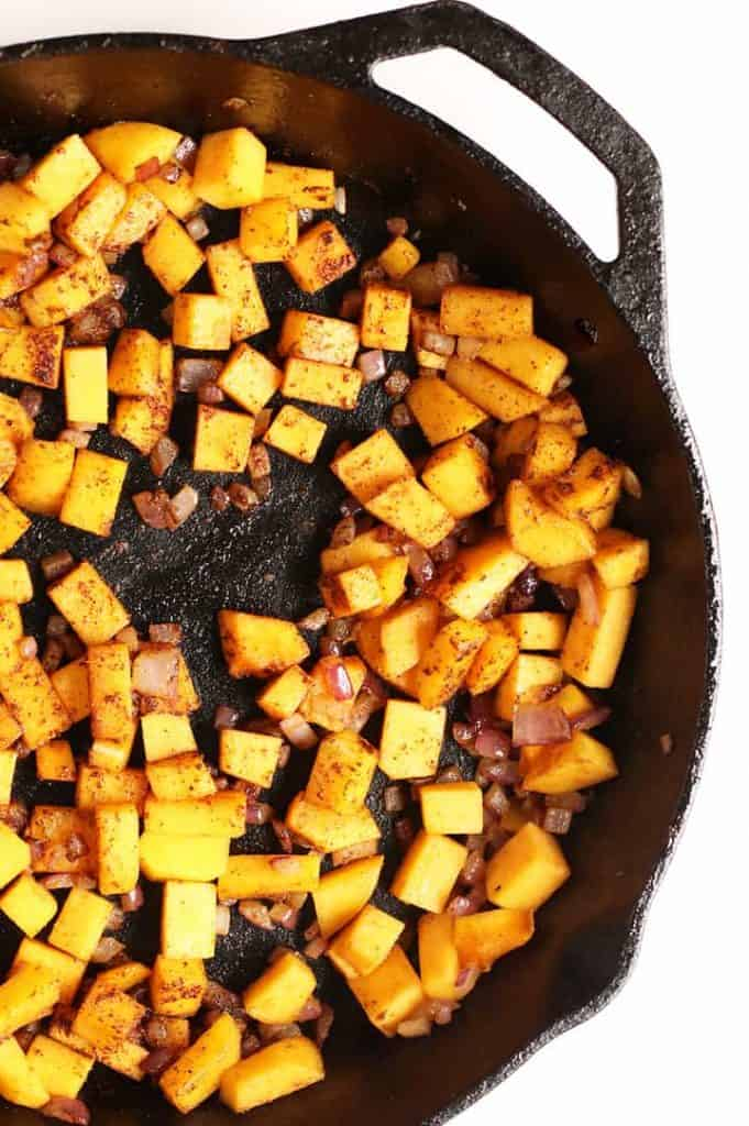 Sautéed onions and squash in a cast iron skillet