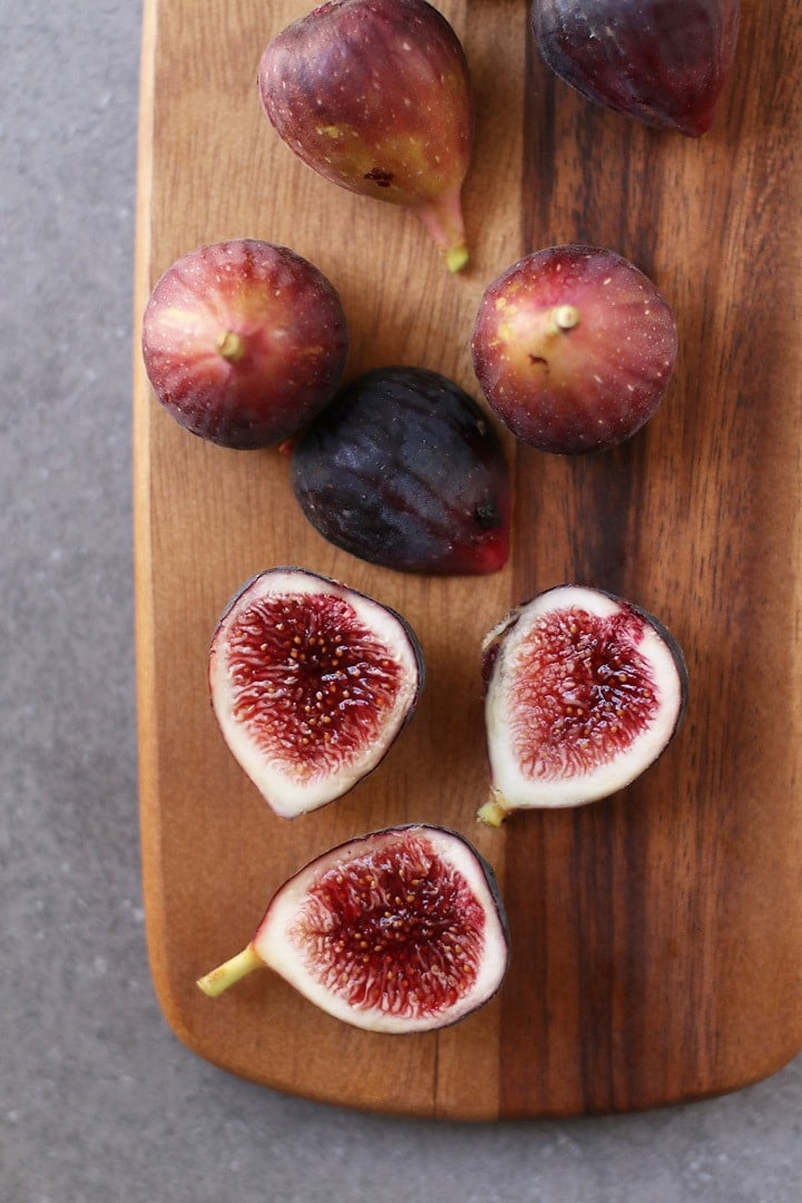 Whole and halved figs on a wooden platter