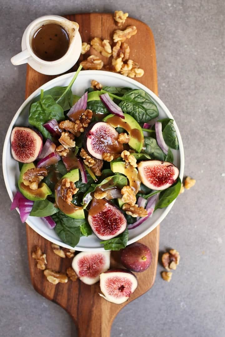 Fig Spinach Salad with balsamic vinaigrette on a wooden board.
