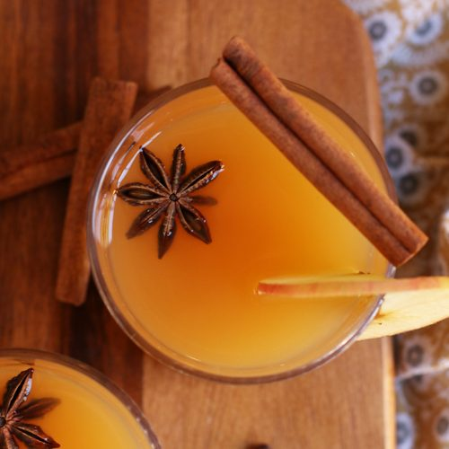 Orange Spiced Bourbon in a cocktail glass with a cinnamon stick