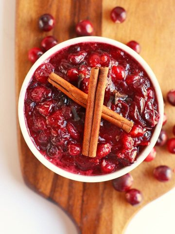Finished cranberry sauce in a white bowl with two cinnamon sticks