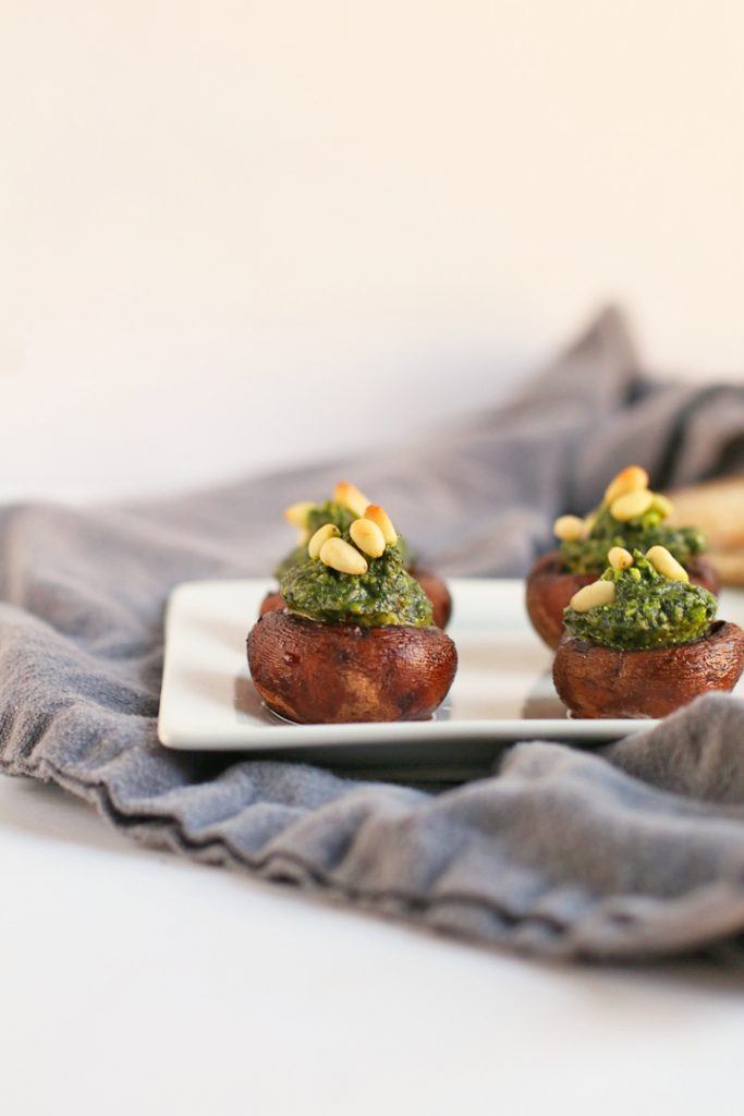 Pesto stuffed mushrooms on a white plate