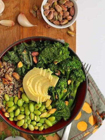 Broccoli, edamame, quinoa, and avocado in a small black bowl