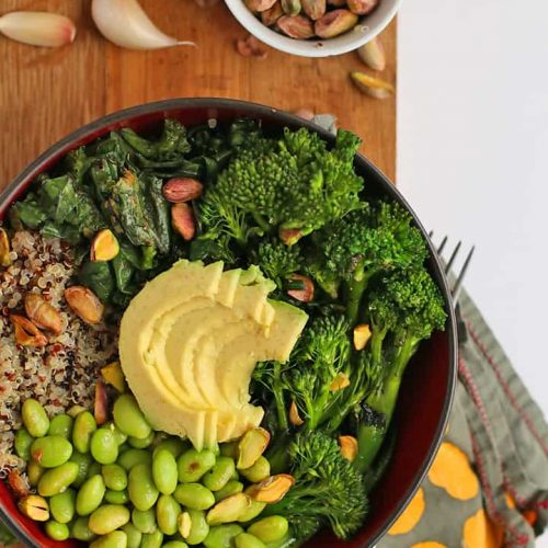 Broccoli, edamame, quinoa, and avocado in a small black bowl