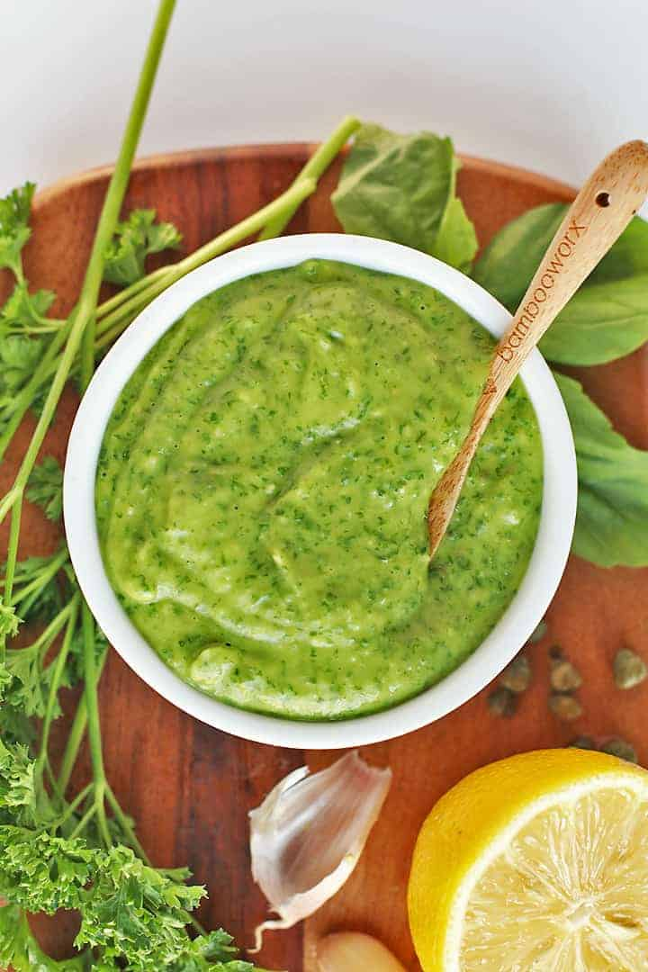 Green Goddess Dressing in a small white bowl with fresh herbs