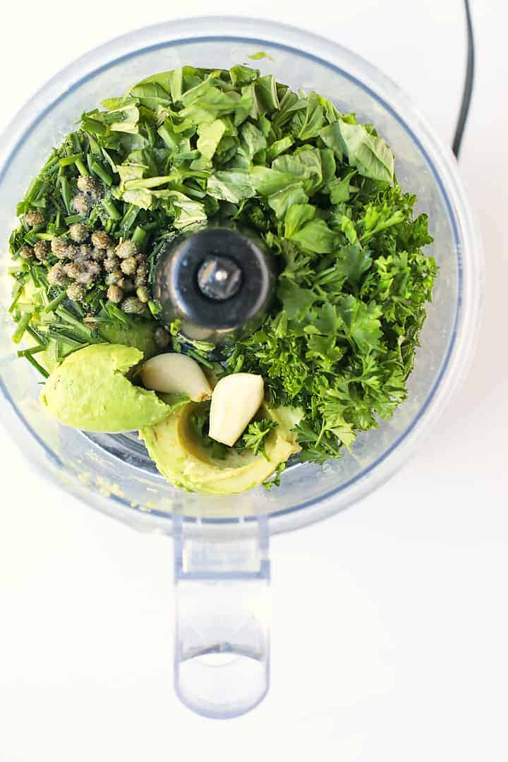 Fresh herbs, avocado, and capers in a food processor.