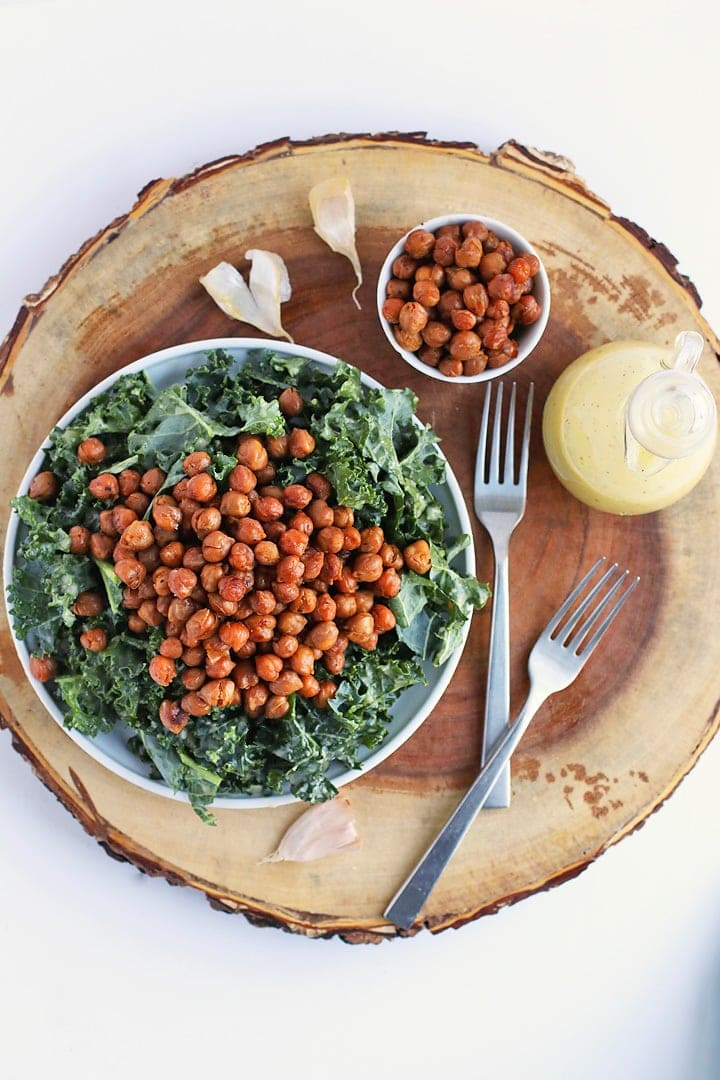 Kale Salad with bacon flavored chickpeas on a wooden platter