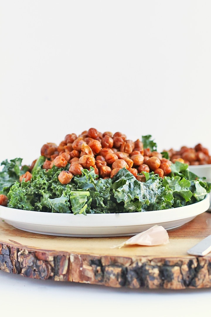 Kale Salad with bacon flavored chickpeas on a white plate