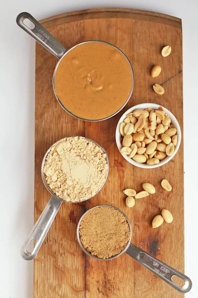 Peanut butter, peanut flour, and peanuts on a wooden board