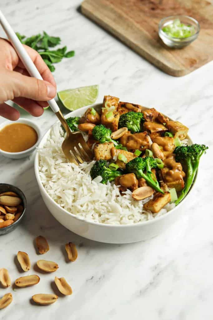 Finished tofu dish served with rice and broccolini in a white bowl.