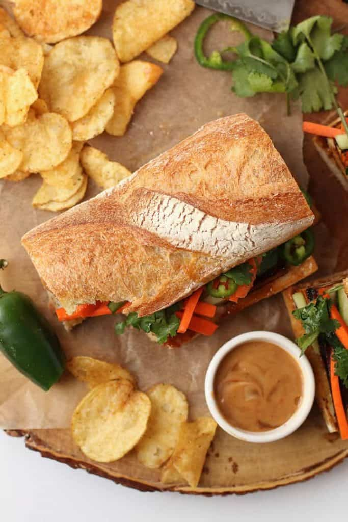 Finished Bahn mi sandwich on a wooden board with chips