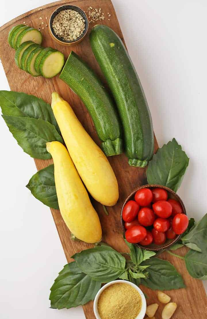 Zucchini, summer squash, and cherry tomatoes on a cutting board