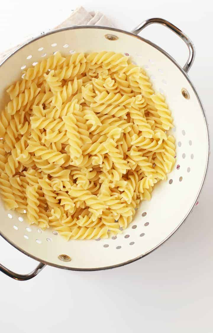 Cooked fusilli pasta in a white cast iron skillet