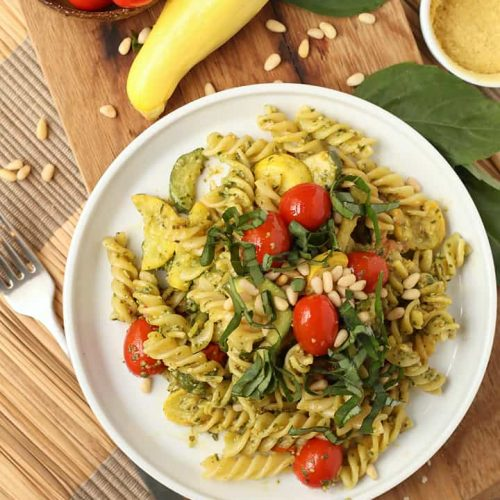 Vegan pesto pasta on a white plate with cherry tomatoes
