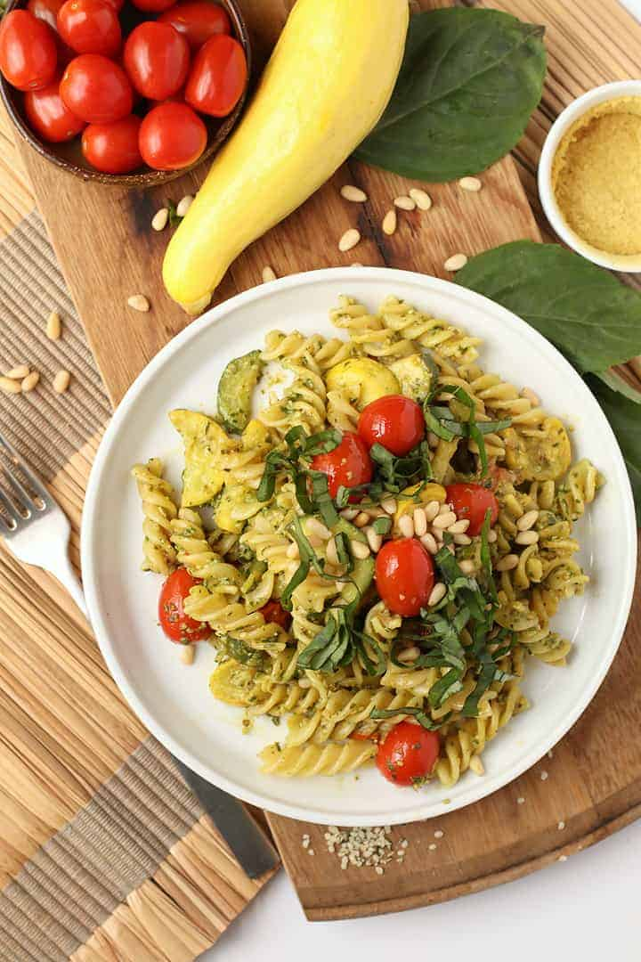 Vegan pesto pasta on a white plate with cherry tomatoes