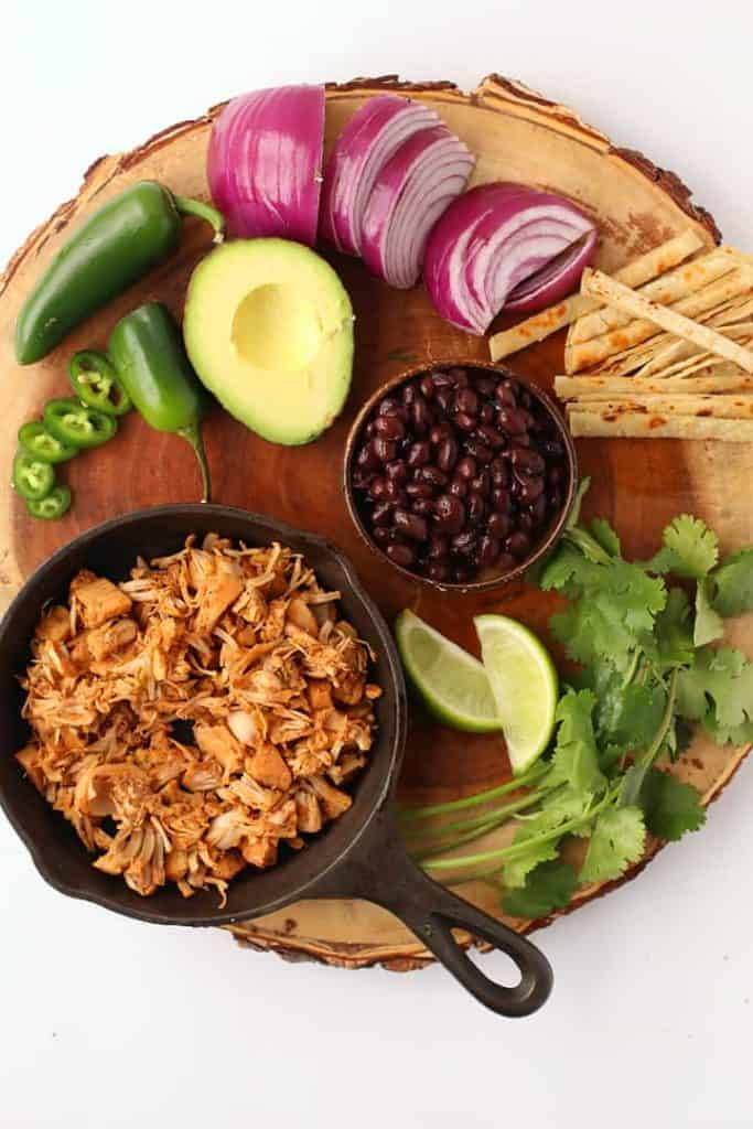 Jackfruit, black beans, avocado, and onions on a wooden platter