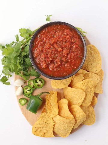Homemade salsa on a wooden platter with tortilla chips