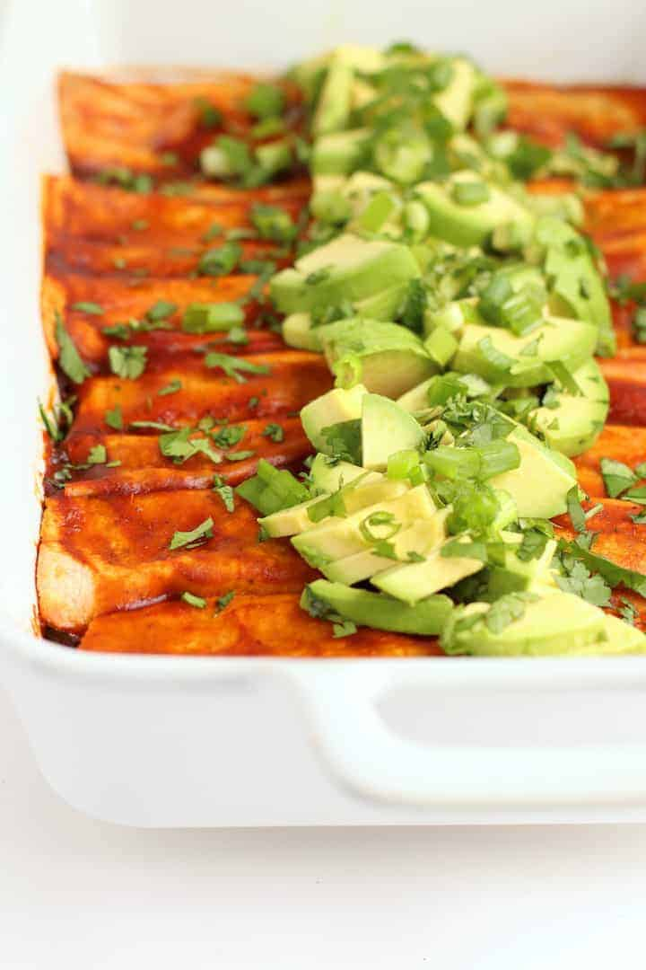 Kale and Black Bean Enchiladas in a white casserole dish