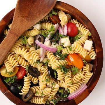 Finished salad in a wooden salad bowl with wooden spoon