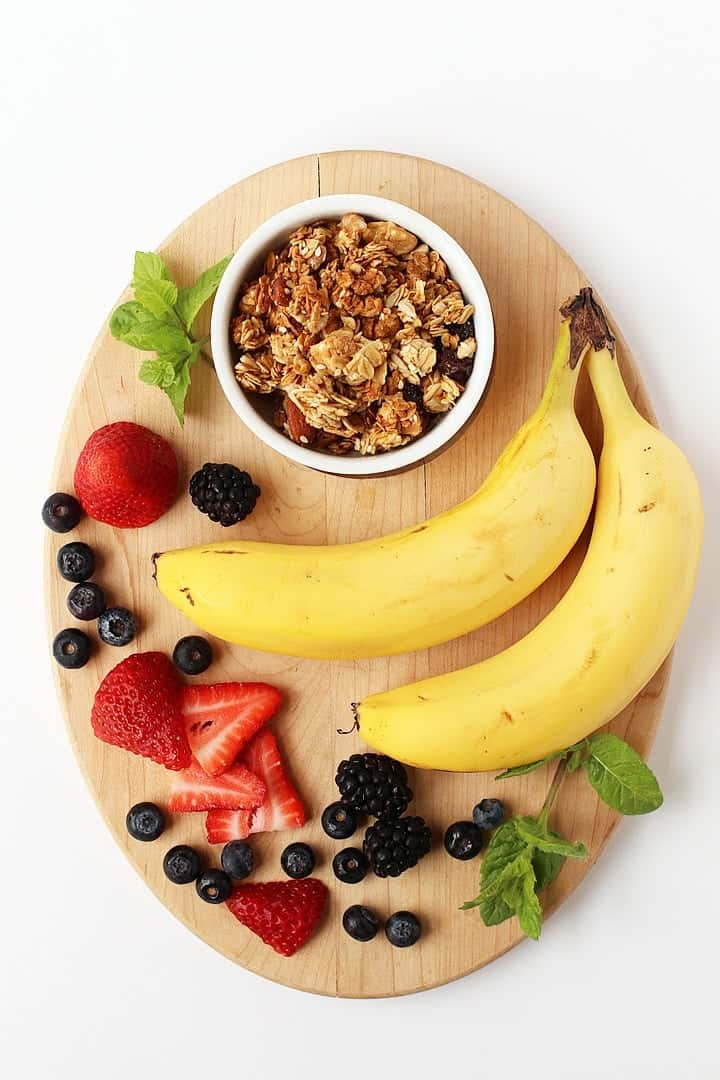 Bananas, berries, and granola on a wooden platter.