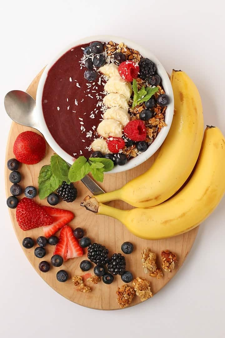 Smoothie bowl on a wooden platter with berries and bananas