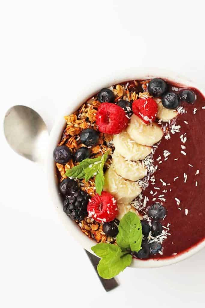Mixed Berry Acai Bowl with granola, bananas, berries, and fresh mint.