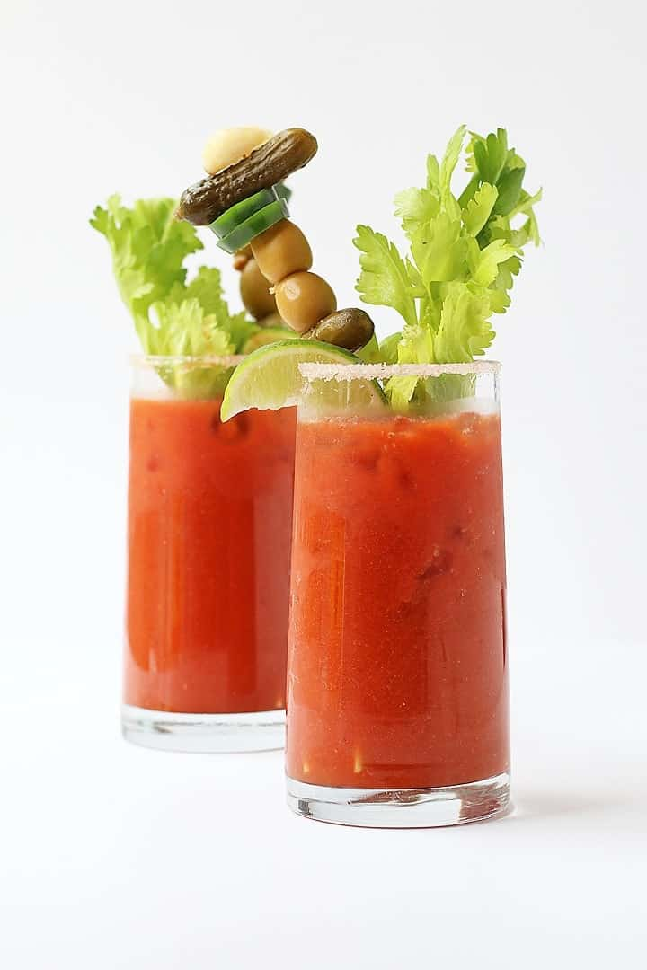 Bloody Mary's on white background with garnish.