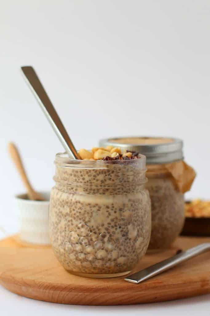Two jars of chia pudding on a wooden platter