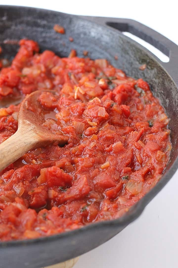 Homemade Marinara Sauce in a skillet with a wooden spoon
