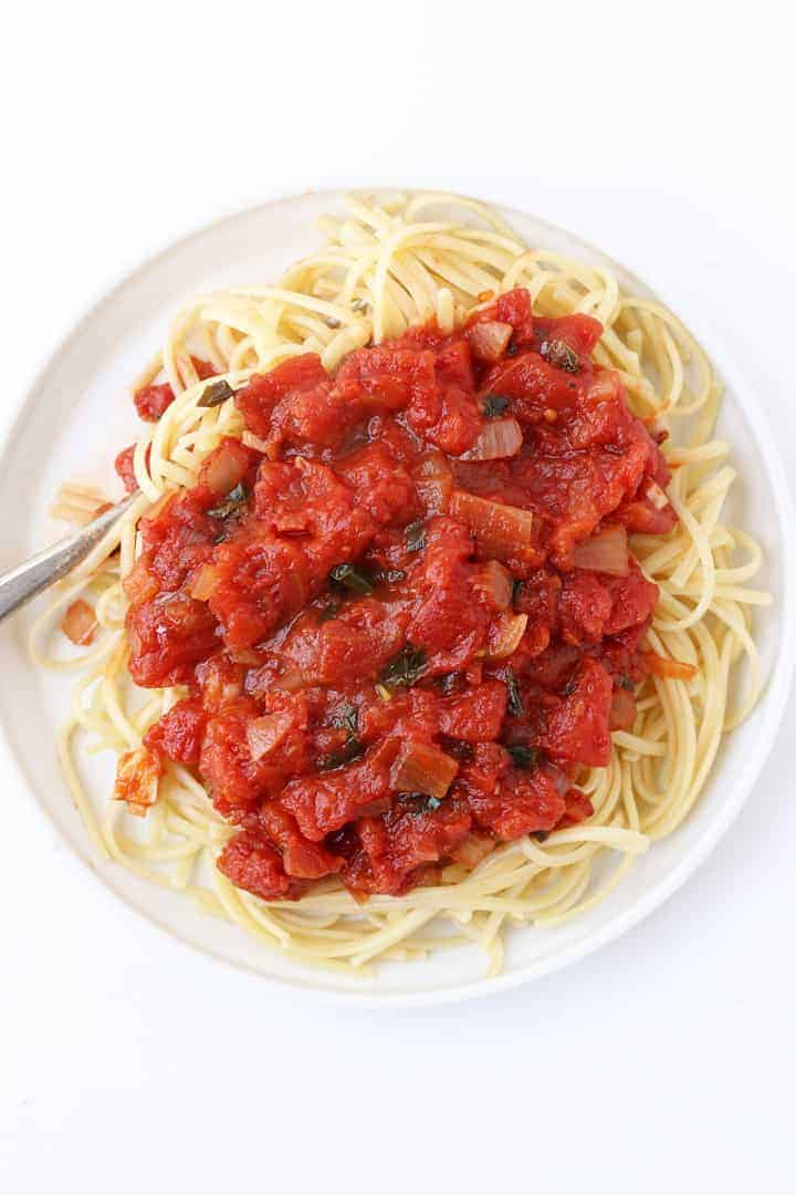 Homemade Marinara Sauce over pasta on a white plate.