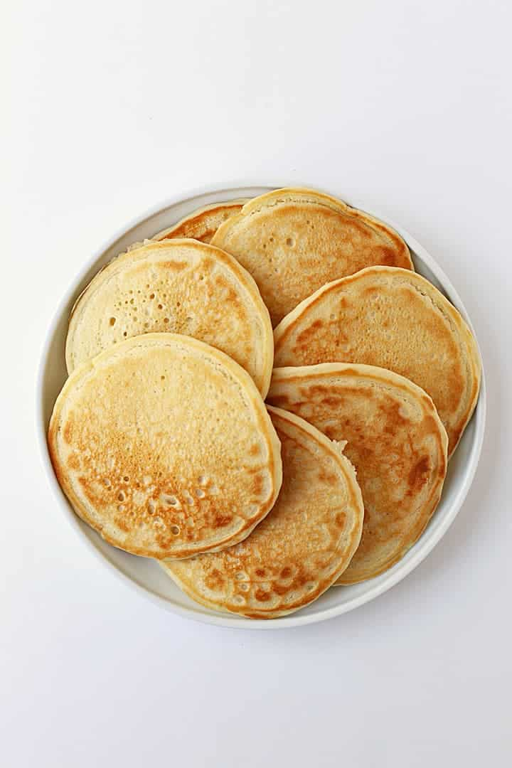 Plate of vegan pancakes on a white background.