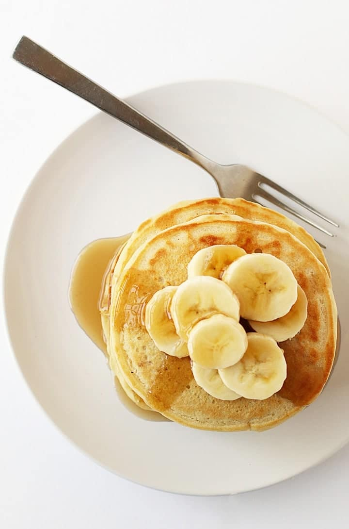 Overhead shot of vegan pancakes on a white plate with a fork.