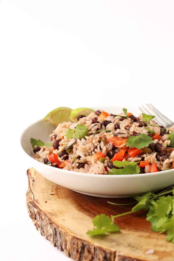 Black Beans and Rice in a white bowl on a wooden platter.