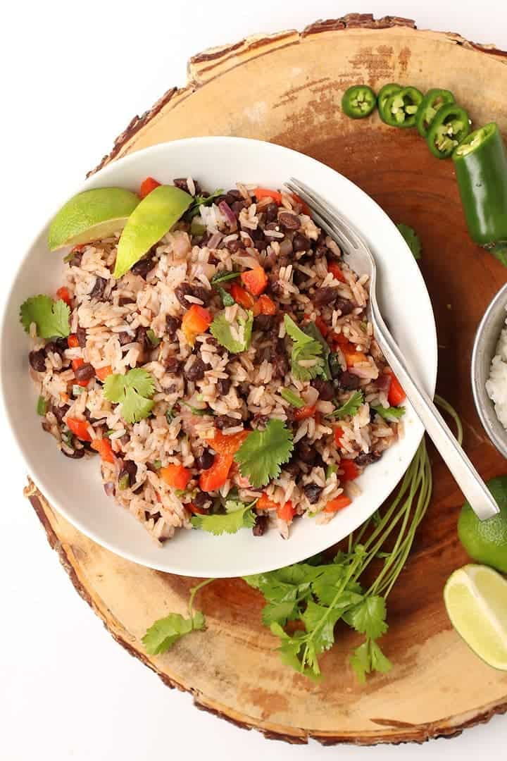 Black Beans and Rice in a white bowl next to cilantro and jalapeño.