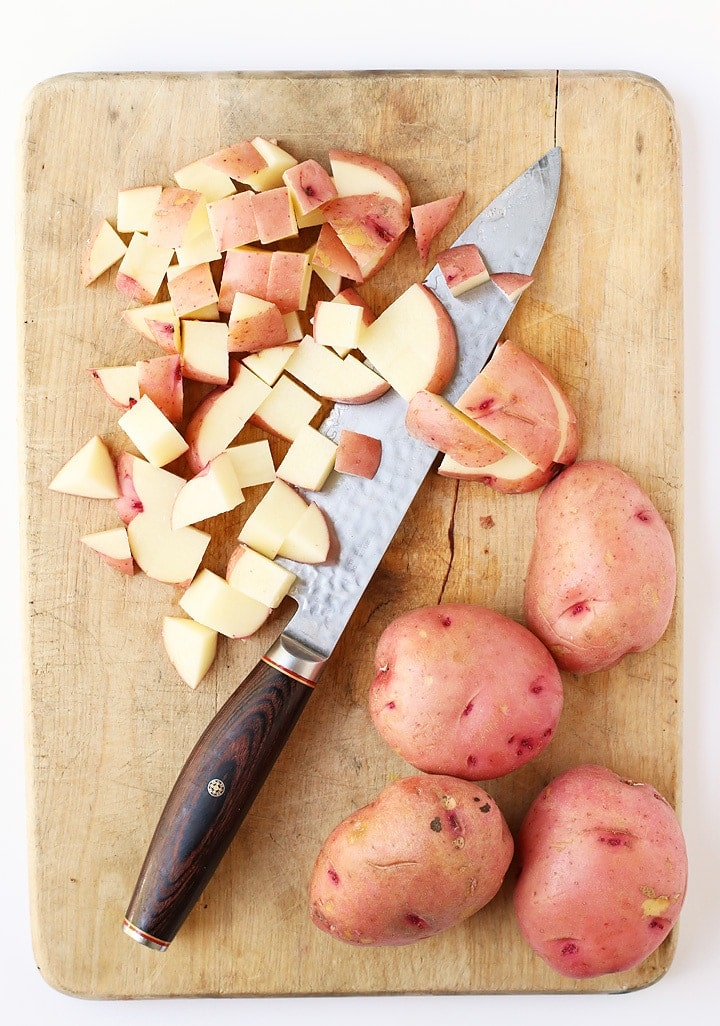 Chopped red skin potatoes on a cutting board with a knife.