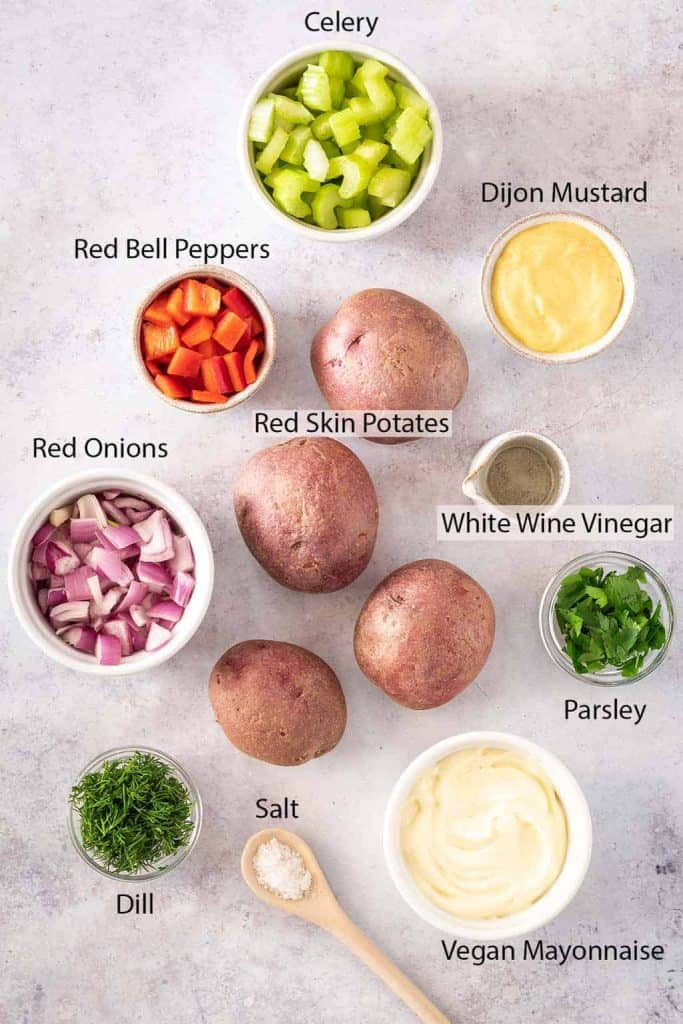 All the ingredients for the potato salad chopped and laid out on a marble countertop
