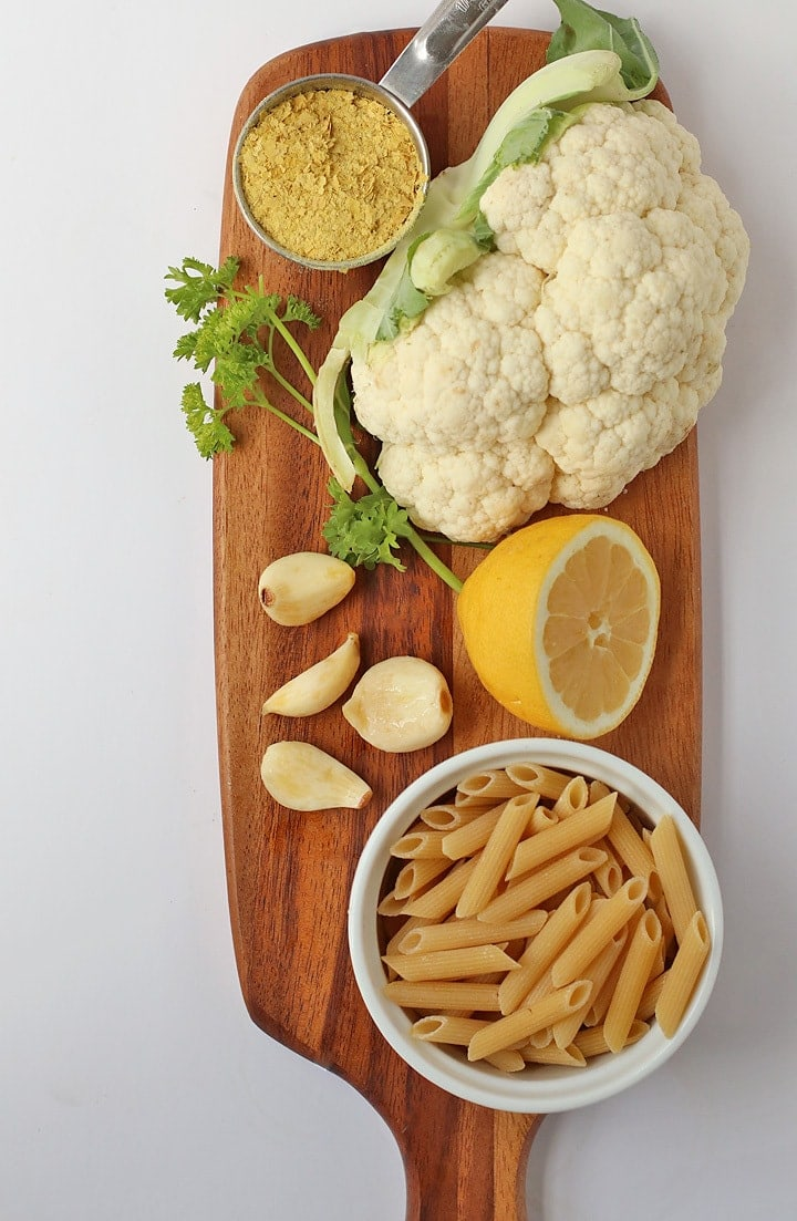 Ingredients for Creamy Garlic Sauce on a wooden cutting board.
