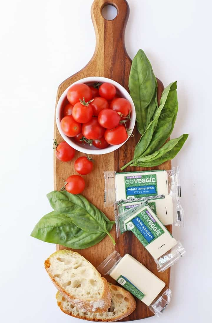 Ingredients for Tomato Basil Bruschetta on a cutting board.