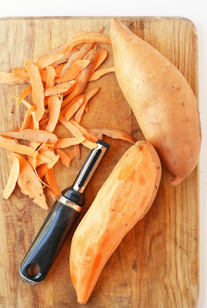 Peel sweet potatoes on a cutting board with a vegetable peeler.