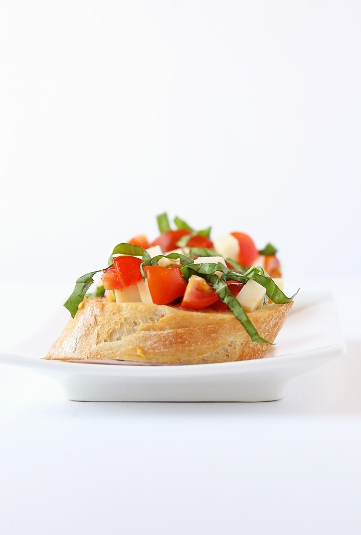 Tomato Basil Bruschetta on a white plate with a white background.