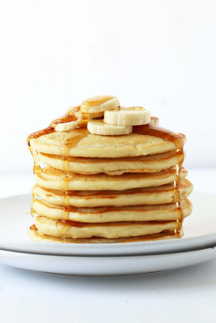 Stack of vegan pancakes with maple syrup and bananas