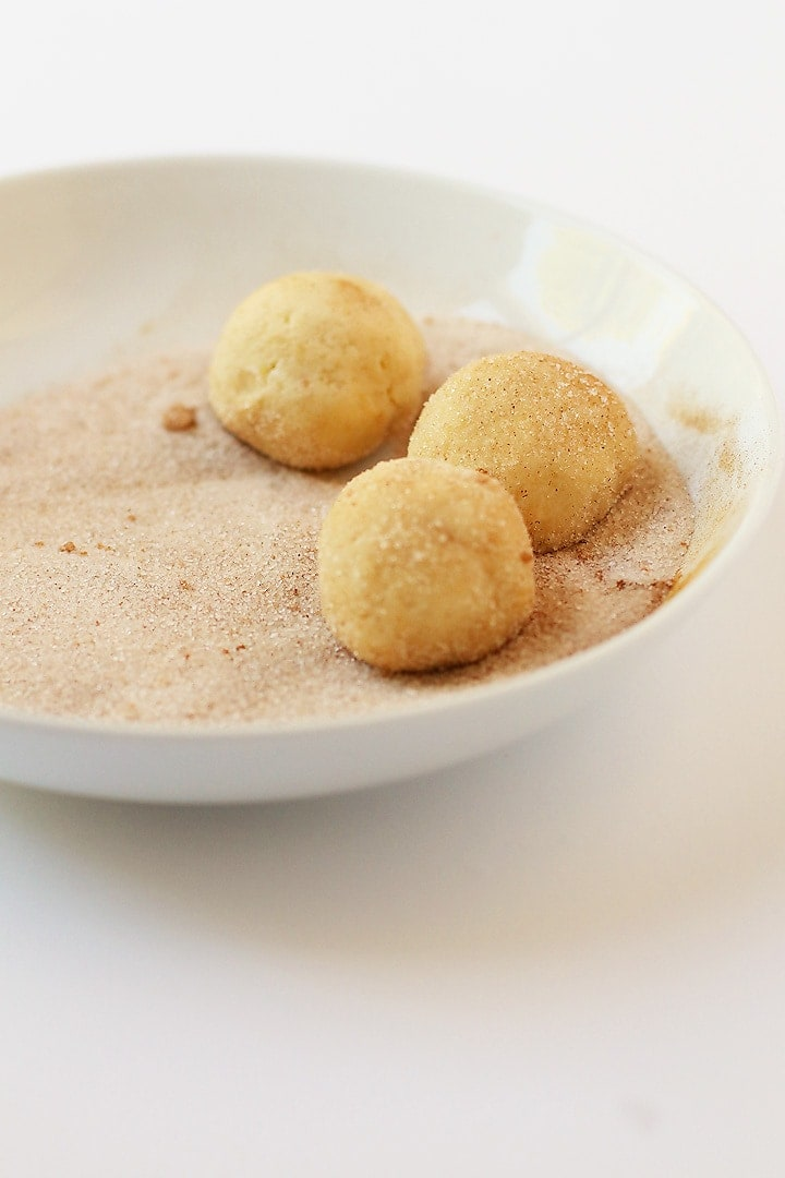 Vegan Snickerdoodles rolled into balls in cinnamon sugar