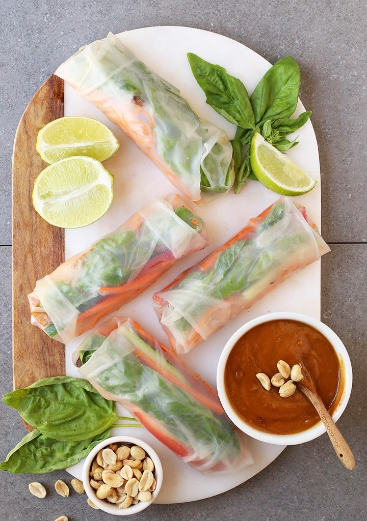 Fresh Vegan Spring Rolls on a marble platter with peanut sauce and lime