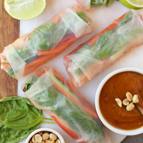 Finished spring rolls on a platter with peanut sauce