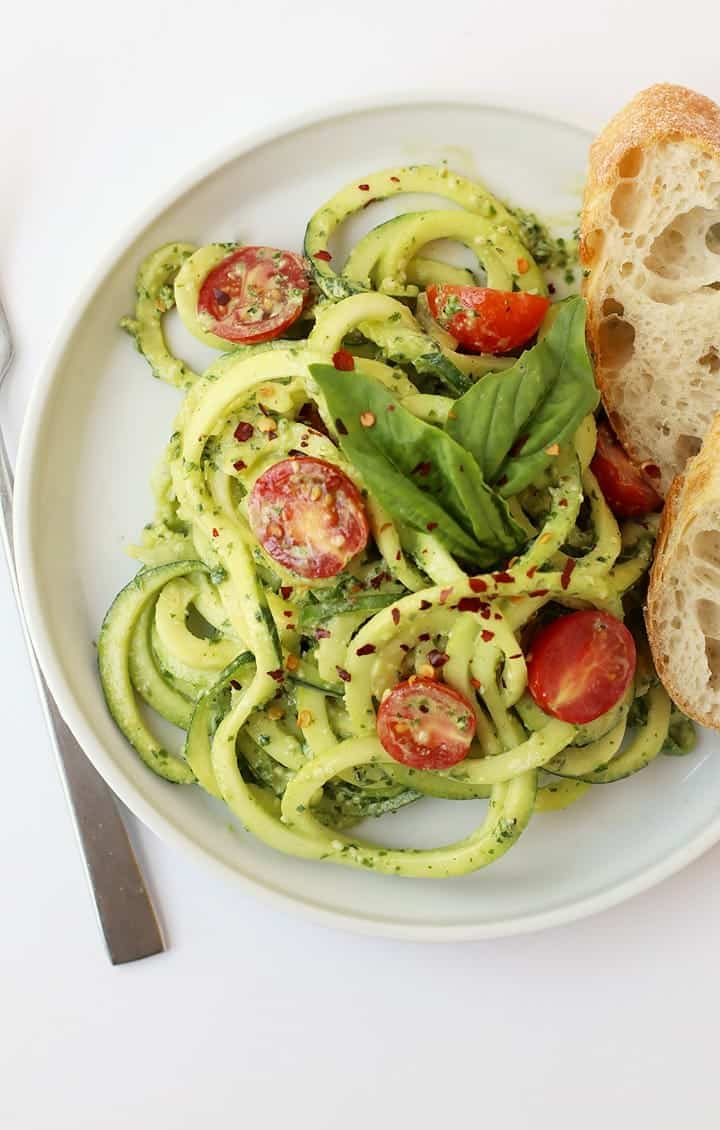 Close up of Zucchini Noodles with Pesto on a white plate with a fork.