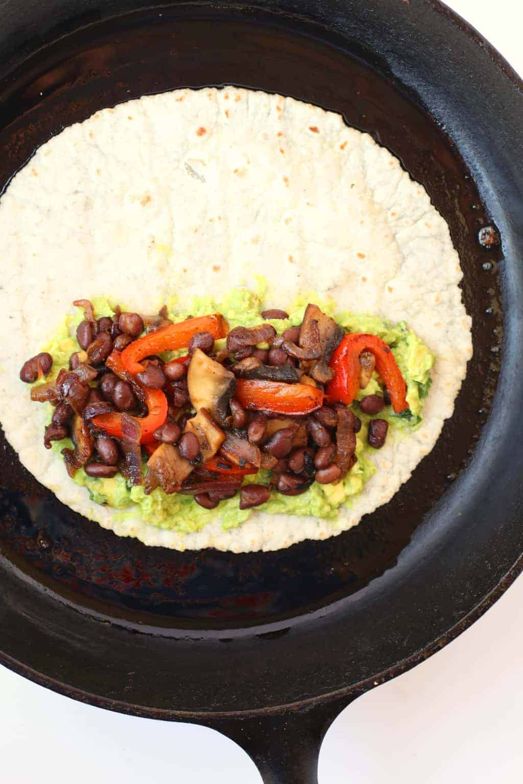Tortilla with beans and veggies in a cast iron skillet