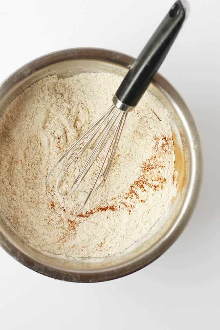 Flour and spices in a bowl with a whisk.