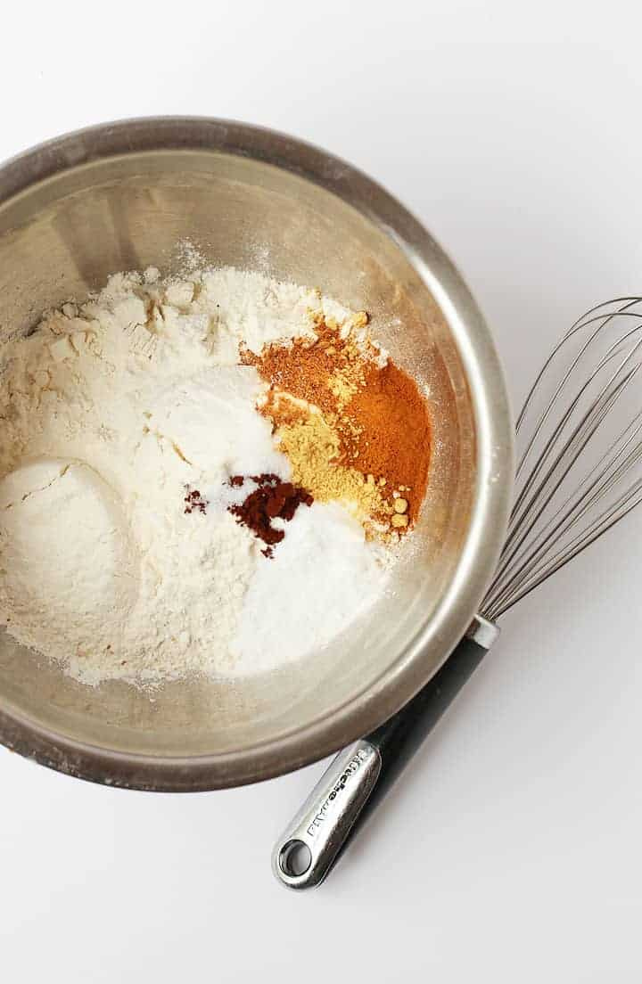 Dry ingredients for pumpkin muffins in a metal bowl with a whisk.